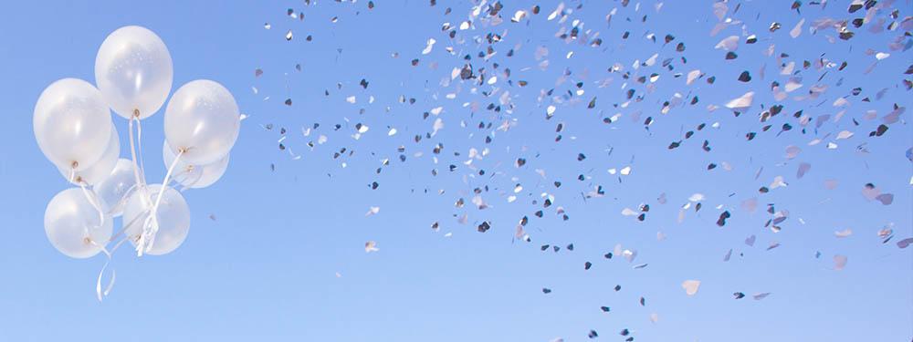 Photo de confettis et de ballons s'envolant dans le ciel bleu