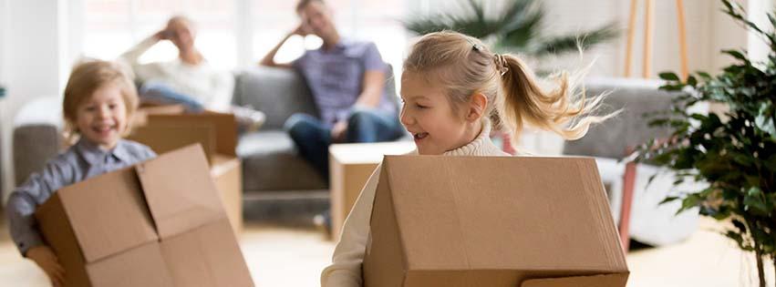 Photo d'une famille en train de déménager avec des enfants en train de porter des cartons