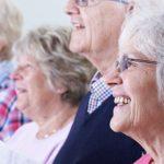 Photo de plusieurs seniors en ligne en train de chanter partitions en main