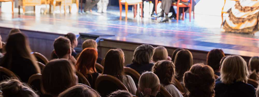 Photo montrant des spectateurs assis devant une pièce de théâtre