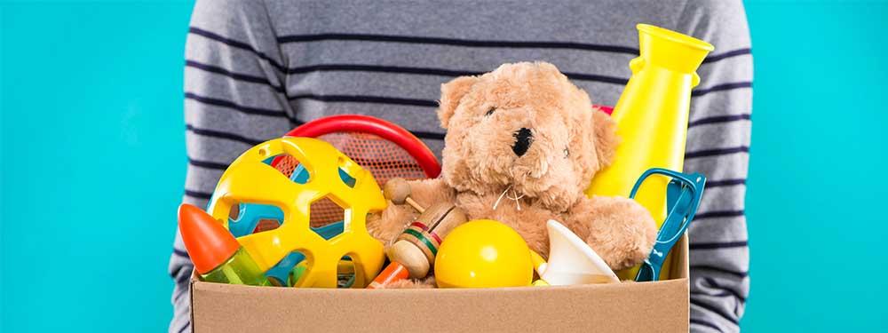 Photo d'un adulte portant une carton de jouets dans les mains