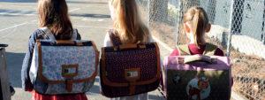 Photo montrant 3 élèves de dos sac sur le dos