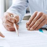 Photo montrant les bras et des mains sur un bureau en train de relire des documents