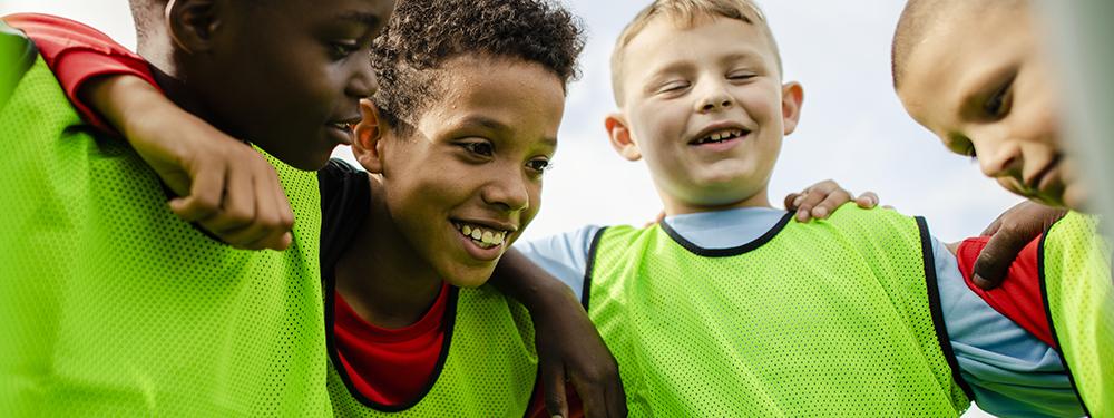 Photo montrant des jeunes footballeurs en train de se serrer dans les bras