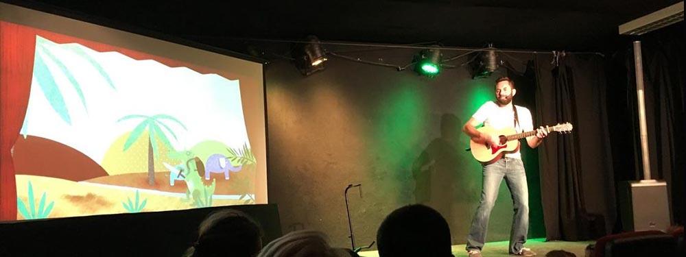 Photo de rémi le roi des comptines sur une scène avec une guitare