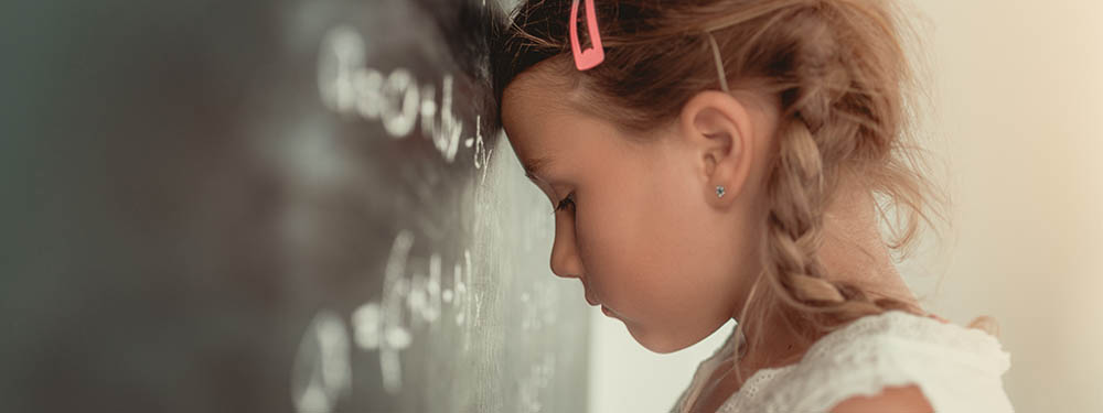 Photo montrant une élève mécontente le front collé contre le tableau noir