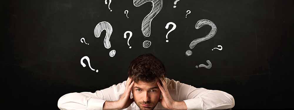 Photo d'un homme se tenant la tête avec des points d'interrogation au dessus de lui