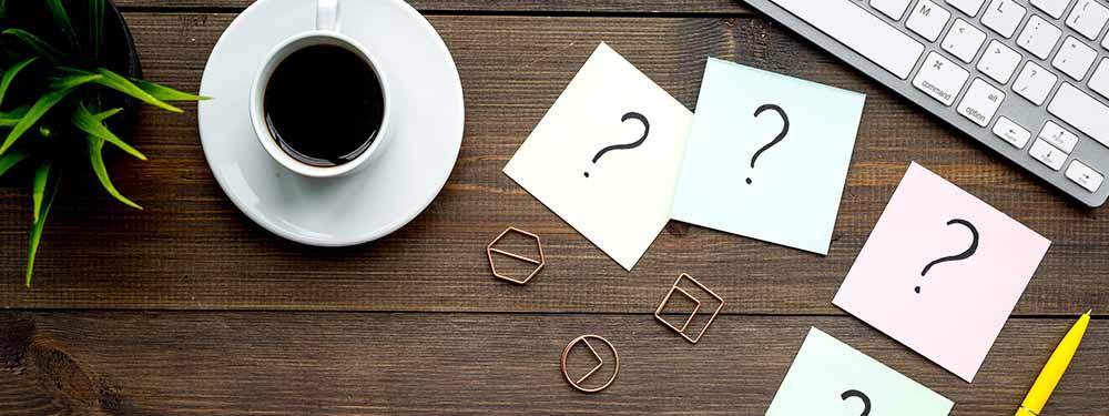Photo d'un bureau vu de haut avec un tasse à café et des points d'interrogation sur des post-its