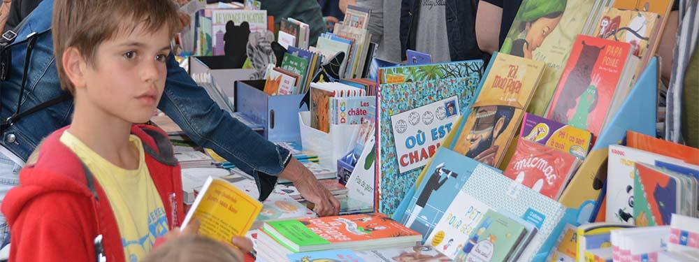Photo du salon du livre jeunesse montrant un enfant devant un stand de livres