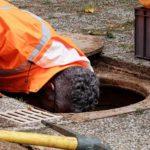 Photo d'un agent des services publics en train de réparer les réseaux d'assainissement