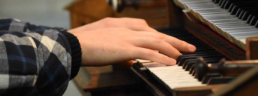 Photo montrant les mains d'un jeune homme jouant de l'orgue