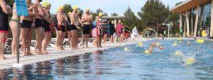 Photo de nageurs lors du triathlon de l'espoir encouragés par d'autres nageurs