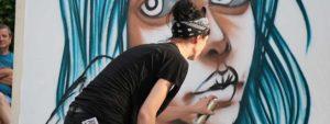 Photo du street nécessaire montrant une artiste en train de faire une oeuvre à la bombe en direct