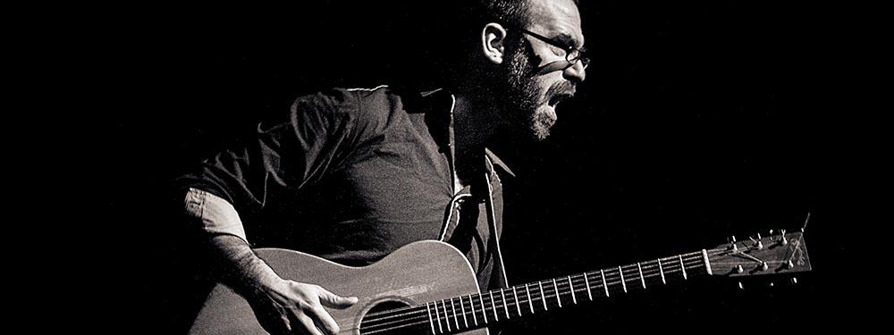 Photo de Erwan Pinard sur scène avec sa guitare en main