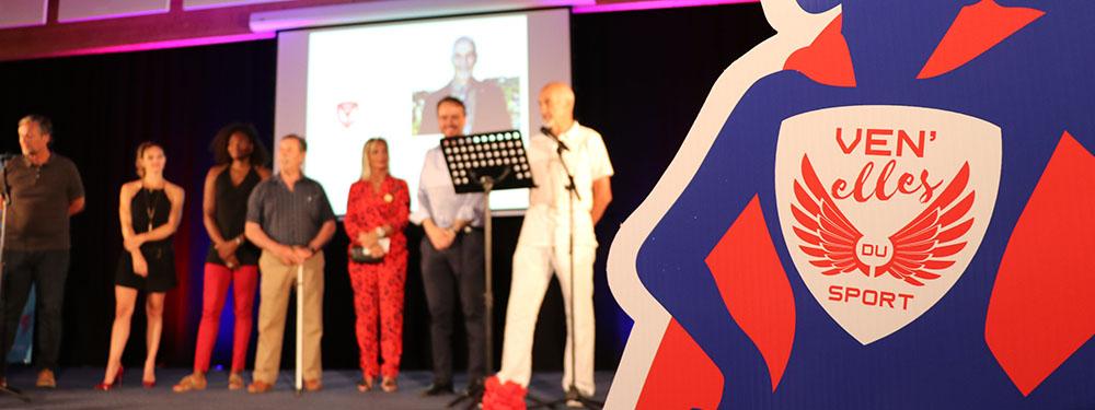 Photo de la scènce des Ven'elles du sport avec les élus en fond et le logo de l'évènement au premier plan