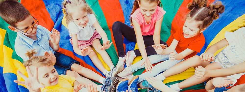 Photo d'enfant assis sur une couverture multicolor en train de jouer
