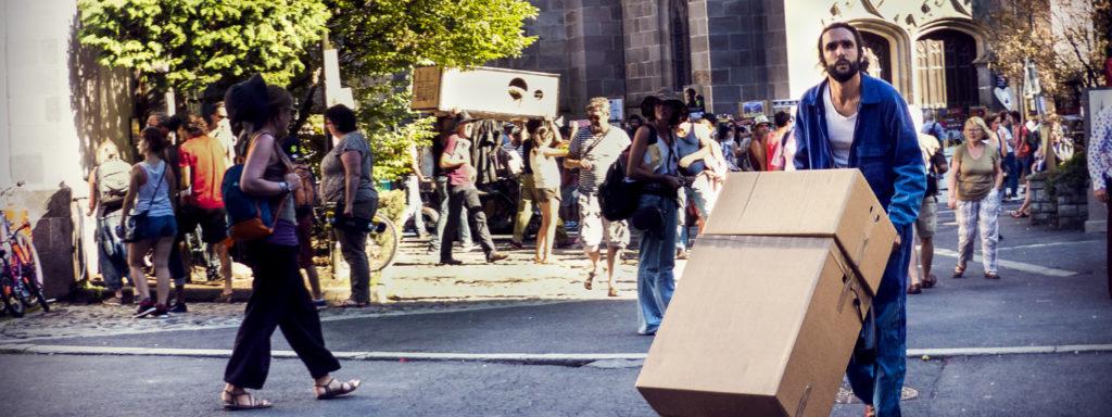 Photo représentant un déménageur en bleu de travail, en plein centre ville. Il transporte deux cartons sur un diable.