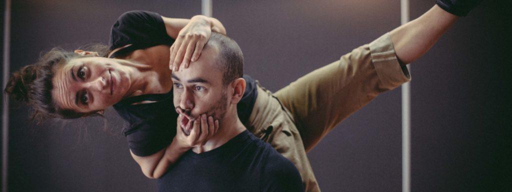 Photo représentant les deux artistes. La femme réalise une acrobatie sur l'épaule de l'homme tout en le faisant grimacer