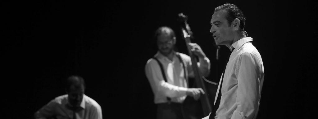 Photo en noir et blanc représentant le chanteur en chemise cravate. Au fond deux musiciens: contrebasse et guitare.