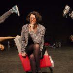 Photo représentant une femme assise sur un fauteuil rouge avec un regard dubitatif. Les deux danseurs qui l'entourent réalisent une figure Hip Hop