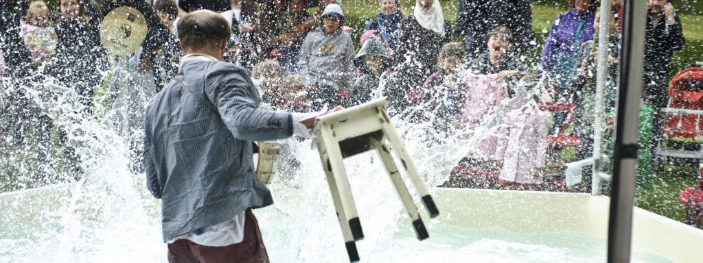 Photo représentant une homme dans une piscine qui éclabousse le public. Il tient dans ses mains un tabouret