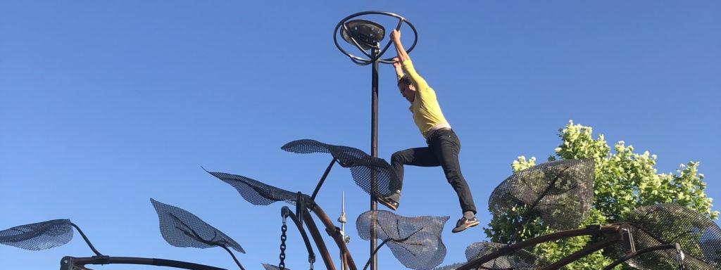 Photo représentant une trapéziste suspendue à un mât de manège