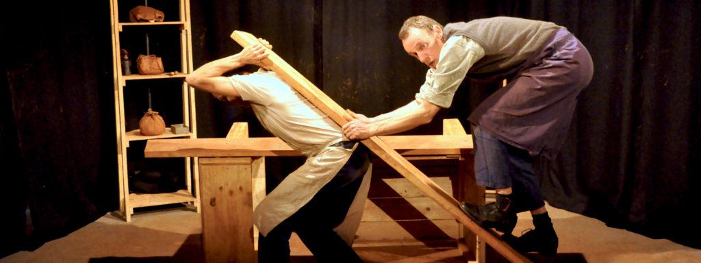 Photo représentant 2 personnages dans un atelier de potier. Muni d'une planche de bois, l'un escalade le dos de l'autre.