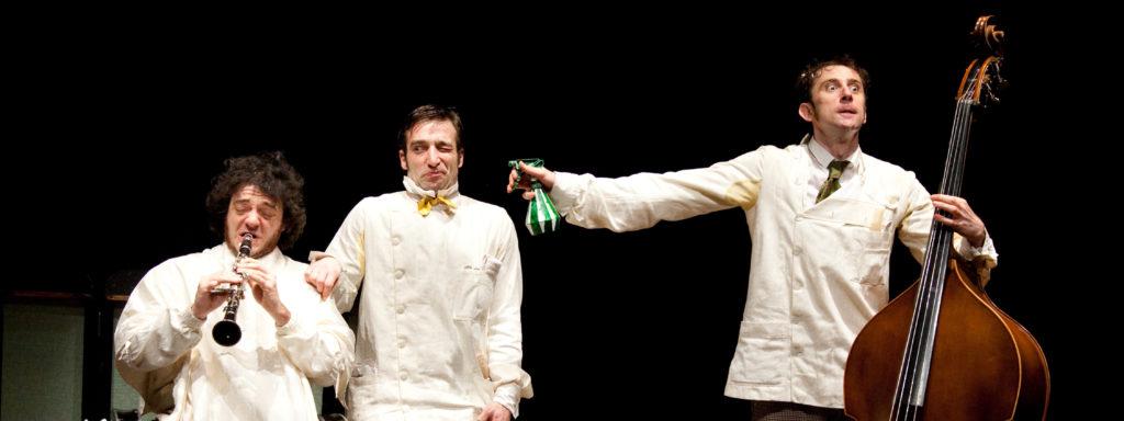 Photo représentant trois personnages en tenue de barbiers, l'un joue de la clarinette, l'autre fait le pitre, le dernier asperge les deux autre tout en jouant de la contrebasse