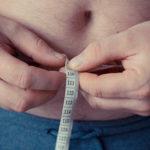 Photo montrant un homme avec du ventre mesurant son tour de ventre avec un mètre