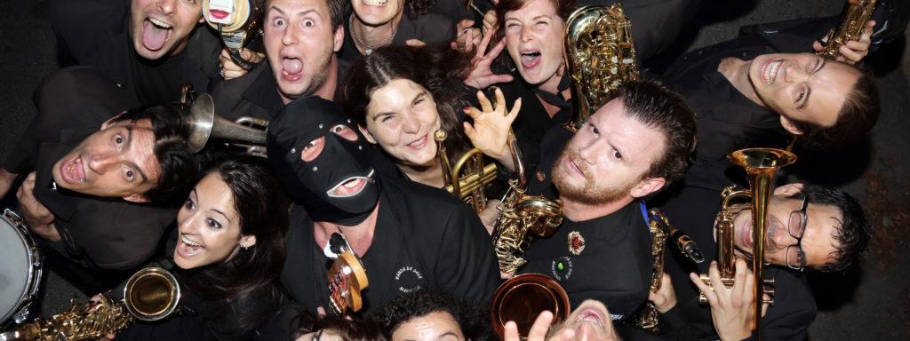 Photo représentant les 13 musiciens vêtus de noir en contre plongé