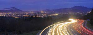 Photo d'une autoroute de nuit avec toutes les lumières des phares laissant des trainées de lumière