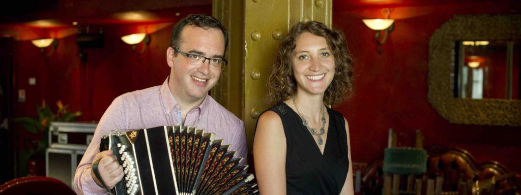 Photo représentant deux musiciens prenant la pose dans un restaurant. Le musicien de gauche tient dans ses mains un bandonéon