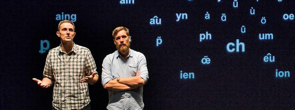 Photo représentant deux hommes en pleine conférence en train de parler. En fond, on distingue sur un écran des syllabes éparpillées