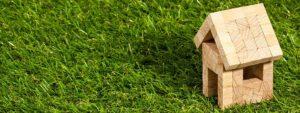 Photo d'une petite maison en bois en jouet posée sur un gazon bien vert