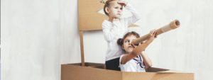 Photo de 2 petites filles en train de jouer aux pirates dans un bateau en carton