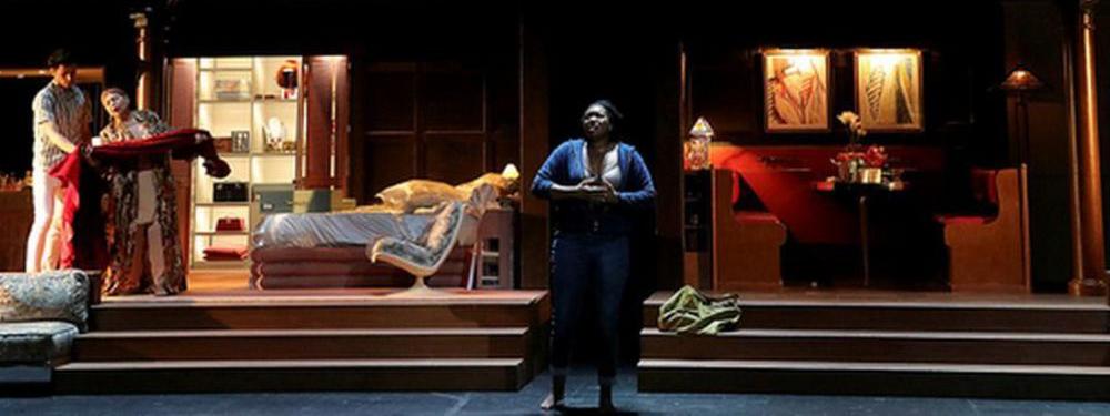 Photo représentant une femme qui chante en premier plan, en second plan on aperçoit un décor de salle à manger et chambre avec deux personnages
