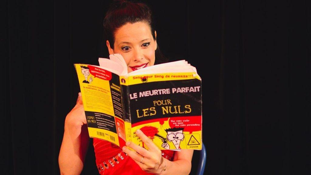 """Photo de la pièce de théâtre Cherie c'est qui le patron montrant une femme lisant un livre """"Le meurtre parfait pour les nuls"""""""