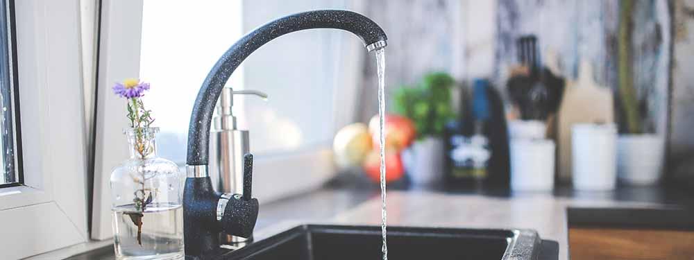 Photo montrant un robinet ouvert dans une cuisine