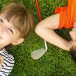 Photo de 2 enfants allongés sur un green de golf