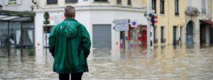 Photo d'un homme debout de dos regardant une ville totalement inondée