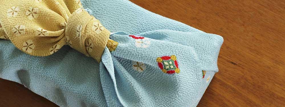 Photo d'un cadeau avec un emballage furoshiki posé sur une table