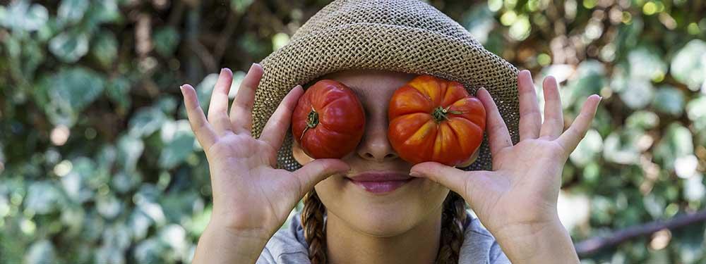 Photo d'une petite fille plaçant 2 tomates à la place de ses yeux