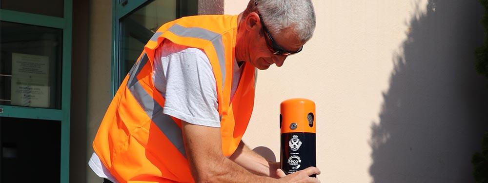 Photo d'un agent des services techniques en train de poser la borne de mégots