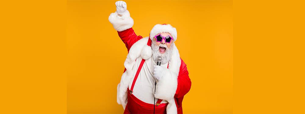 Photo d'un père Noel le point levé, micro à la main avec des lunettes de soleil étoiles roses
