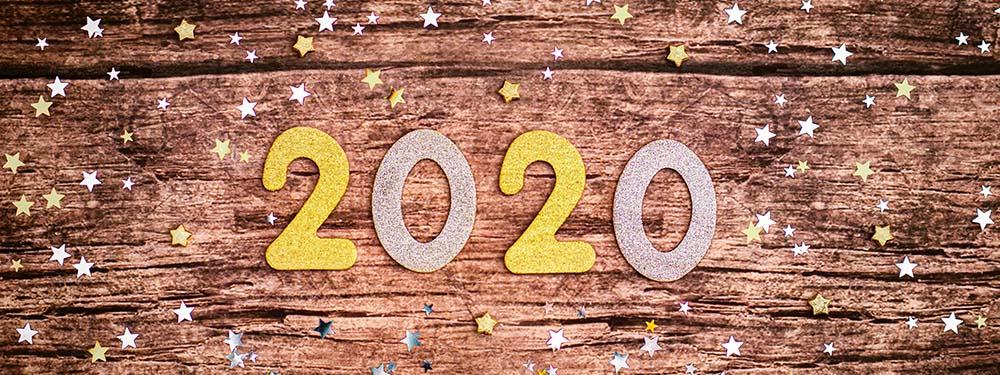 Photo des chiffres 2020 posés sur une table en bois avec des étoiles partout autour