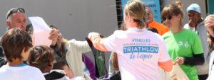 groupe de personnes autour d'un coureur portant un T-shirt Triathlon de l4espoir