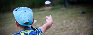 Photo d'un enfant en train de jouer à la pétanque
