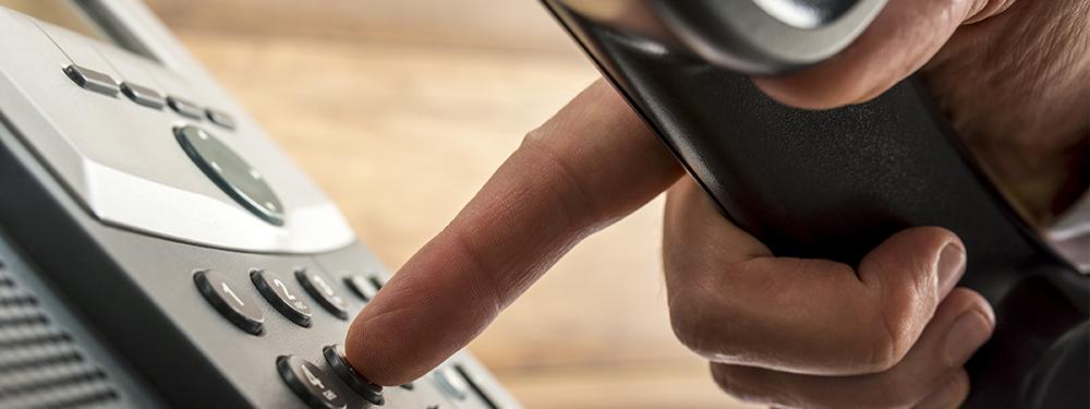 Photo montrant une personne en train de composer un numéro de téléphone sur son combiné
