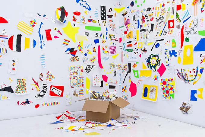 Photo représentant une pièce avec un carton dans un coin. Les murs sont couverts de dessins colorés.