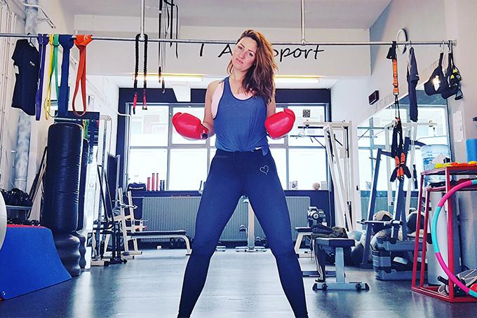 Photo représentant une femme dans une salle de sport. Elle se tient debout et porte des gants de boxe.